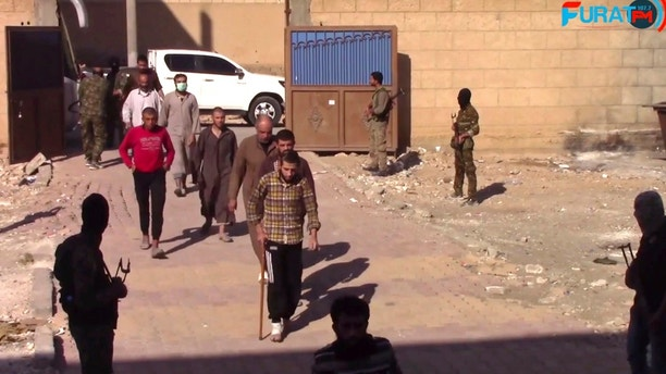 "This frame grab from video released Sunday, Oct. 15, 2017 and provided by Furat FM, a Syrian Kurdish activist-run media group, shows Syrian Islamic State group fighters who surrendered entering a base of the U.S.-backed Syrian Democratic Forces (SDF), in Raqqa, Syria. A spokesman for the SDF in Syria says it will be in control of the northern city of Raqqa ""within a few days"" after attacking the last pocket held by the Islamic State group. SDF fighters launched an operation to retake the last IS-held pocket of Raqqa after some 275 militants and their family members surrendered. (Furat FM, via AP)"