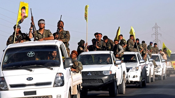 Fighters of Syrian Democratic Forces ride on trucks as their convoy passes in Ain Issa, Syria October 16, 2017. REUTERS/Erik De Castro - RC1477EFDE30