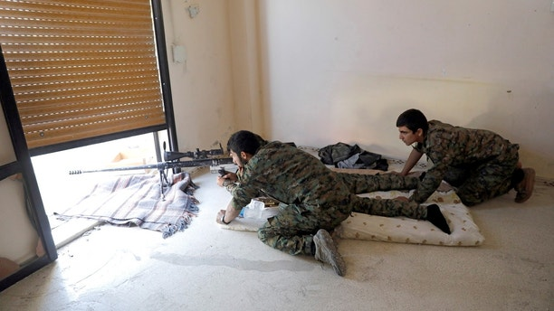 Fighters of Syrian Democratic Forces take up position inside a building opposite the National Hospital where the Islamic State militants are holed up at the frontline in Raqqa, Syria October 16, 2017.      REUTERS/Erik De Castro - RC1EDB201F40
