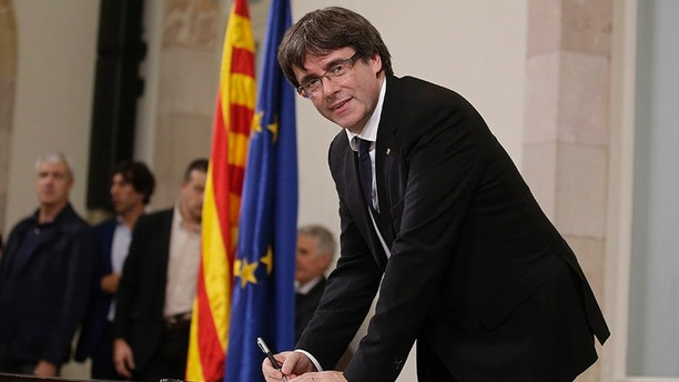 "Catalan regional President Carles Puigdemont signs an independence declaration document after a parliamentary session in Barcelona, Spain, Tuesday, Oct. 10, 2017. Puigdemont says he has a mandate to declare independence for the northeastern region, but proposes waiting ""a few weeks"" in order to facilitate a dialogue. (AP Photo/Manu Fernandez)"