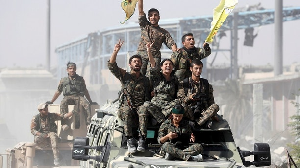 Syrian Democratic Forces (SDF) fighters ride atop military vehicles as they celebrate victory in Raqqa, Syria, October 17, 2017. REUTERS/Erik De Castro TPX IMAGES OF THE DAY - RC18150D4560
