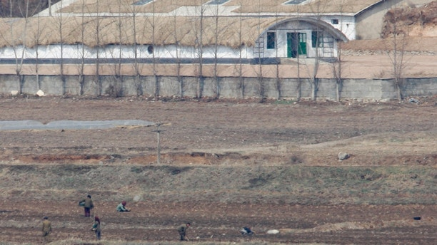 North Koreans work on a field in the propaganda village of Gijungdong near the truce village of Panmunjom in the demilitarized zone in Paju, 42 km (26 miles) northwest of Seoul, that separates North Korea from the South March 26, 2008. South Korea's new conservative government wants North Korea to answer questions about the fate of its prisoners of war and abducted civilians believed to be still held by the communist state, officials said on Tuesday.  REUTERS/Lee Jae-Won (SOUTH KOREA) - RTR1YR7R