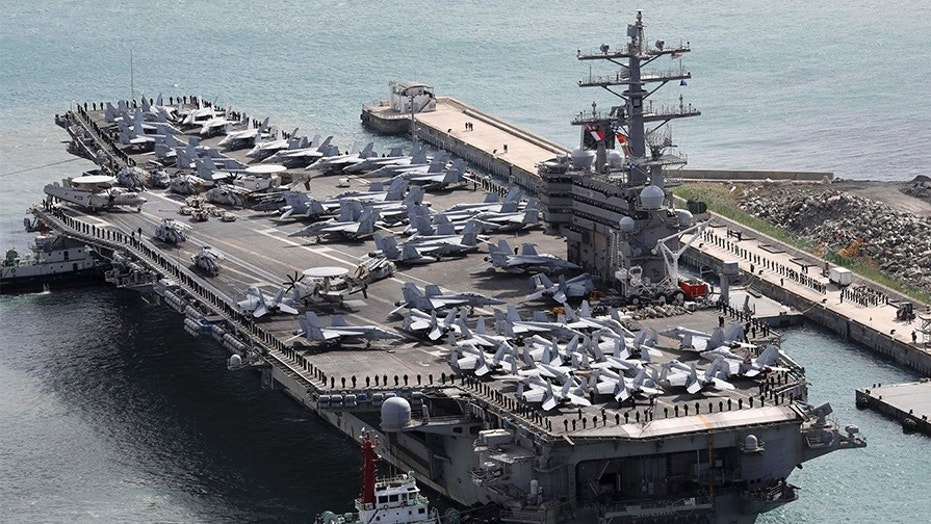 The aircraft carrier USS Ronald Reagan (CVN 76) is escorted into Busan port, South Korea, after completing a joint drill with the South Korean military, Saturday.