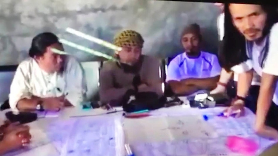 FILE - This file image taken from undated video shown to The Associated Press by the Philippine military shows the purported leader of the Islamic State group Southeast Asia branch, Isnilon Hapilon, center, at a meeting of militants at an undisclosed location.