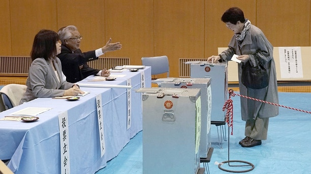 A voter casts her ballot in a general election at a polling station in Tokyo Sunday, Oct. 22, 2017. Voting has kicked off for Japan's general election on Sunday that would most likely hand Prime Minister Shinzo Abe's ruling coalition a win, possibly retaining two-thirds in the parliament. (AP Photo/Eugene Hoshiko)