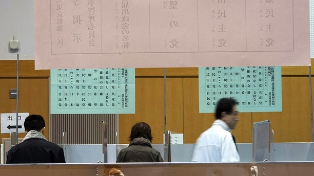 Voter fill their ballots in a general election at a polling station in Tokyo Sunday, Oct. 22, 2017. Voting has kicked off for Japan's general election on Sunday that would most likely hand Prime Minister Shinzo Abe's ruling coalition a win, possibly retaining two-thirds in the parliament. (AP Photo/Eugene Hoshiko)