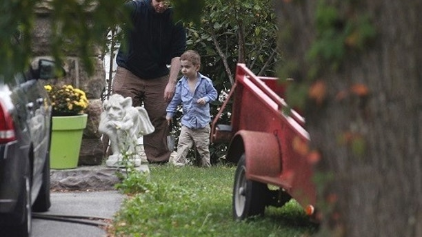 ADDS NAME OF SON JONAH-Joshua Boyle and his son Jonah play in the garden at his parents house in Smiths Falls, Ont., on Saturday, Oct. 14, 2017. A couple held hostage for five years by a Taliban-linked network and forced to raise three children while in captivity were initially targeted for ransom because of the impending birth of their first child, the Canadian man at the heart of the case speculated Saturday. Boyle said he and his wife Caitlan Coleman heard at least half a dozen reasons why they had been snatched from a village in Afghanistan and held against their will by the Haqqani network over the years they were imprisoned. (Lars Hagberg/The Canadian Press via AP)