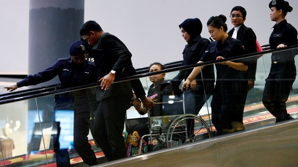 Indonesian Siti Aisyah, who is on trial for the killing of Kim Jong Nam, the estranged half-brother of North Korea's leader, is escorted as she revisits the Kuala Lumpur International Airport 2 in Sepang, Malaysia October 24, 2017. REUTERS/Lai Seng Sin - RC15D9F75B60