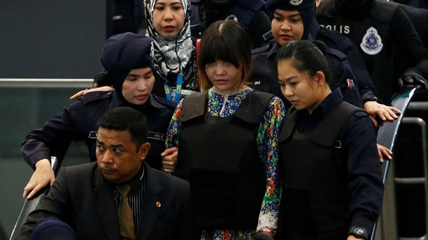 Vietnamese Doan Thi Huong, who is on trial for the killing of Kim Jong Nam, the estranged half-brother of North Korea's leader, is escorted as she revisits the Kuala Lumpur International Airport 2 in Sepang, Malaysia October 24, 2017. REUTERS/Lai Seng Sin - RC1776CEA950