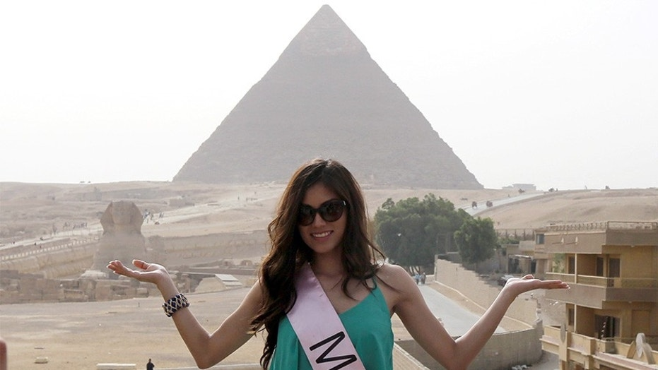 A contestant of Miss ECO Universe poses for a picture with pyramids behind, on the outskirts of Cairo, Egypt, April 10, 2016.  REUTERS/Mohamed Abd El Ghany - D1AESXYKFRAA
