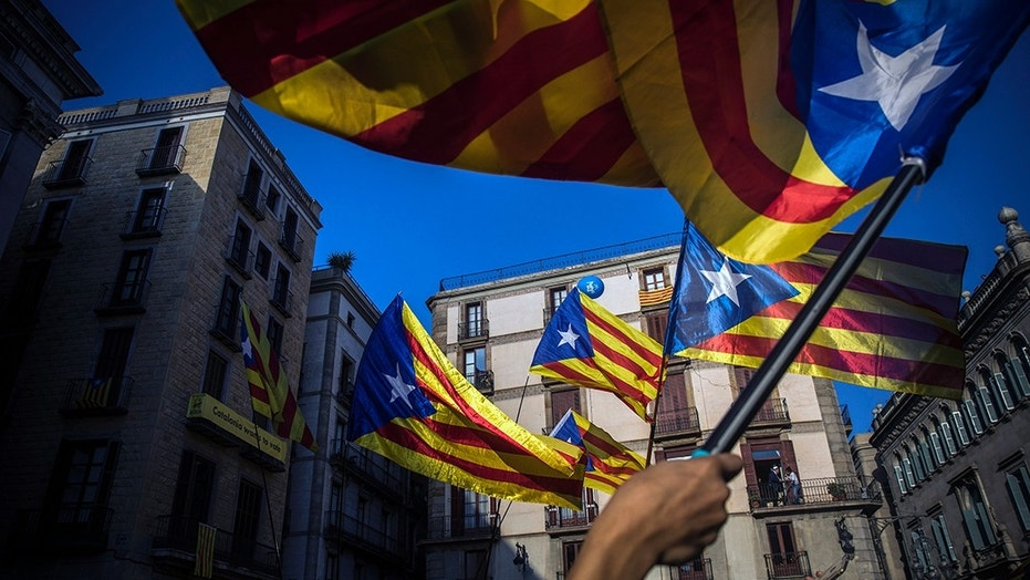 People wave Catalan flags in Barcelona Thursday after the regional president's address.