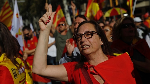 A nationalist protester gestures before the start of a mass rally against Catalonia's declaration of independence, in Barcelona, Spain, Sunday, Oct. 29, 2017. Thousands of opponents of independence for Catalonia are holding the rally on one of the city's main avenues after one of the country's most tumultuous days in decades. (AP Photo/Santi Palacios)