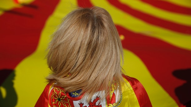 A woman draped in a Spanish flag stands by a giant Catalan flag before the start of a mass rally against Catalonia's declaration of independence, in Barcelona, Spain, Sunday, Oct. 29, 2017. Thousands of opponents of independence for Catalonia are holding the rally on one of the city's main avenues after one of the country's most tumultuous days in decades. (AP Photo/Santi Palacios)