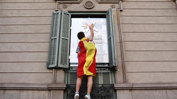 A youth draped in a Spanish flag puts flag stickers on a Caixabank building before a mass rally against Catalonia's declaration of independence, in Barcelona, Spain, Sunday, Oct. 29, 2017. Thousands of opponents of independence for Catalonia are holding the rally on one of the city's main avenues after one of the country's most tumultuous days in decades.(AP Photo/Gonzalo Arroyo)