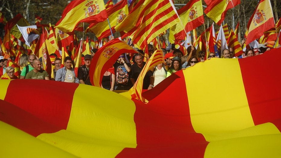 Nationalist activists protest with Spanish and Catalan flags during a mass rally against Catalonia's declaration of independence in Barcelona, Spain, Sunday, Oct. 29, 2017.