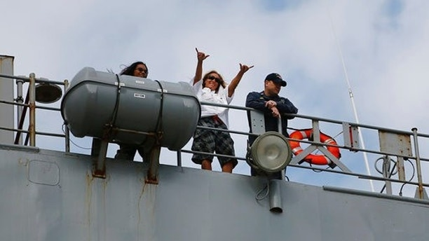 Jennifer Appel, center, raises her arms from bridge way of the USS Ashland Monday, Oct. 30 at White Beach Naval Facility in Okinawa, Japan. At left is Tasha Fuiava, and at right the Ashland's Command Master Chief Gary Wise. The U.S. Navy ship arrived at the American Navy base, five days after it picked up the women and their two dogs from their storm-damaged sailboat, 900 miles southeast of Japan. (AP Photo/Koji Ueda)