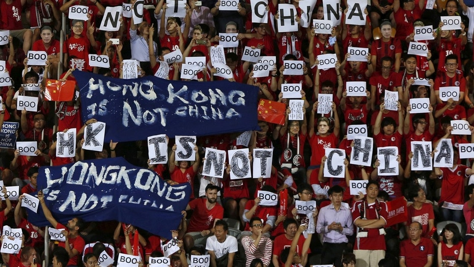 "FILE: Hong Kong fans hold banners and character signs which read ""Hong Kong is not China"", during the 2015 World Cup qualifying match between Hong Kong and China, in Hong Kong."