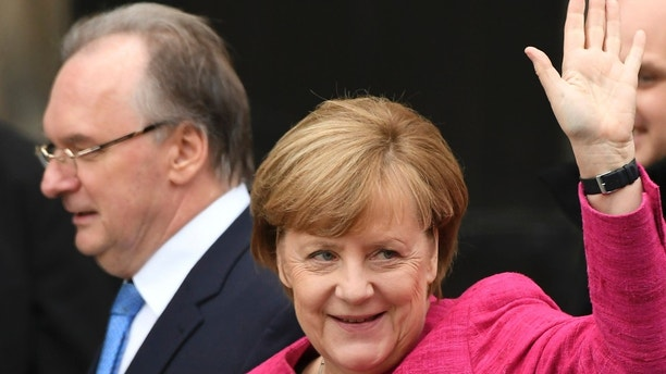 Saxony-Anhalt governor Reiner Haseloff, left, and German Chancellor Angela Merkel arrive for the  official ceremony on the occasion of the 500th Reformation anniversary in Wittenberg, Germany, Tuesday, Oct. 31, 2017. German leaders mark the 500th anniversary of the day Martin Luther is said to have nailed his theses challenging the Catholic Church's practice of selling indulgences to a church door, a starting point of the Reformation. (Hendrik Schmidt/dpa via AP)