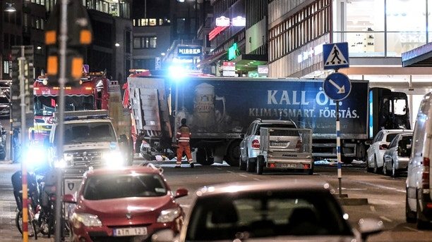 Tow trucks move the beer truck that crashed into the department store Ahlens after plowing down the Drottninggatan Street in central Stockholm, Sweden, April 7, 2017. Fredrik Sandberg / TT News Agency/via Reuters ATTENTION EDITORS - THIS IMAGE WAS PROVIDED BY A THIRD PARTY. FOR EDITORIAL USE ONLY. NOT FOR SALE FOR MARKETING OR ADVERTISING CAMPAIGNS. THIS PICTURE IS DISTRIBUTED EXACTLY AS RECEIVED BY REUTERS, AS A SERVICE TO CLIENTS. SWEDEN OUT. NO COMMERCIAL OR EDITORIAL SALES IN SWEDEN. NO COMMERCIAL SALES. - RC1AFD030F30