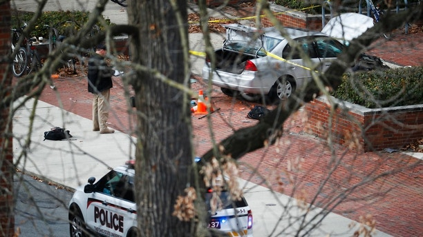A car inside a police line sits on the sidewalk as authorities respond to an attack on campus at Ohio State University, Monday, Nov. 28, 2016, in Columbus, Ohio. Several were injured after a man plowed his car into a group of pedestrians at the university and began stabbing people with a butcher knife Monday before he was shot to death by a police officer. ?(AP Photo/John Minchillo)