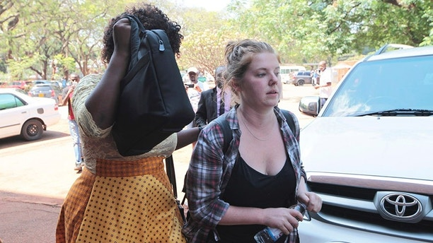 "U.S. Citizen Martha O' Donovan, right, appears at the Harare Magistrates court escorted by a plain clothes police officer shielding her face in Harare, Saturday, November, 4, 2017. Police arrested and charged Donavan with subversion for allegedly insulting President Robert Mugabe on Twitter as a ""sick man,"" lawyers said Friday. The offense carries up to 20 years in prison. (AP Photo/Tsvangirayi Mukwazhi)"