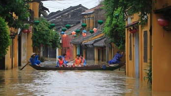 People ride a boat in flooded street in Hoi An, Vietnam, Monday, Nov. 6, 2017. A powerful typhoon that rocked Vietnam has killed dozens of people and caused extensive damage to the country's south-central region ahead of the APEC summit that will draw leaders from around the world, the government said Monday. (AP Photo/Hau Dinh)