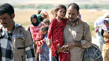 A displaced Yazidi Iraqi carries his daughter as they cross the Syrian border at Fishkhabour. Up to 20,000 people may still be trapped on Mount Sinjar. Photograph: Ahmad al-Rubaye/AFP/Getty