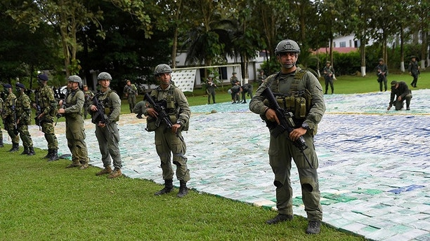 Colombian police and soldiers guard more than 12 tons of seized cocaine in Apartado, Colombia November 8, 2017. Colombian Presidency/Handout via REUTERS    ATTENTION EDITORS -  THIS IMAGE HAS BEEN SUPPLIED BY A THIRD PARTY - RC13A634CC70