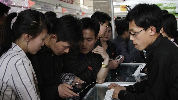 In this May 15, 2013, file photo, North Koreans take a look at the Samjiyon tablet computer produced for the North Korean market for sale at the 16th Pyongyang Spring International Trade Fair in Pyongyang. Ever so cautiously, North Korea is going online. This is all done with a two-tiered system where the trusted elite can surf with relative freedom while the mbades are kept inside the national intranet, painstakingly sealed off from the outside world and meticulously surveilled. (AP Photo/Jon Chol Jin, File)