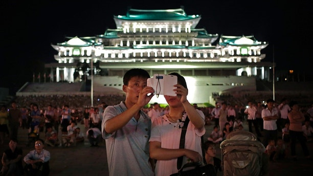 In this Sunday, July 27, 2014, file photo, a North Korean couple use a smartphone to photograph fireworks in at Kim Il Sung Square in Pyongyang, North Korea. Ever so cautiously, North Korea is going online. This is all done with a two-tiered system where the trusted elite can surf with relative freedom while the masses are kept inside the national intranet, painstakingly sealed off from the outside world and meticulously surveilled. (AP Photo/Wong Maye-E, File)
