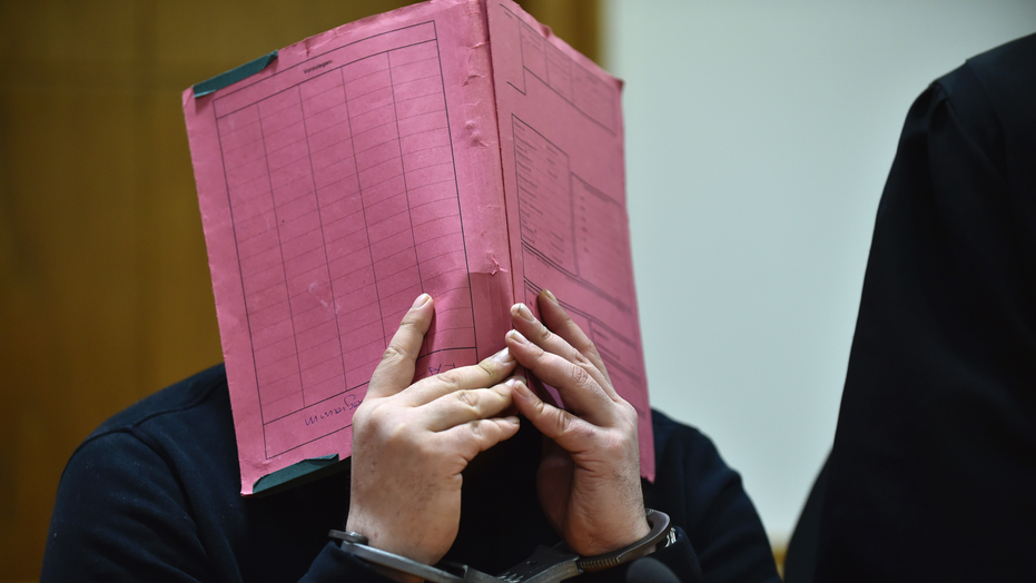 Niels Hoegel covering his face during his trial at the regional court in in Oldenburg, northern Germany, in 2015.