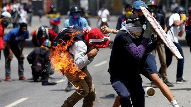 A demonstrator gets himself on fire when he tries to hurl a molotov cocktail as others run during a protest against Venezuela's President Nicolas Maduro's government in Caracas, Venezuela July 10, 2017. REUTERS/Andres Martinez Casares - RC1C1F928770