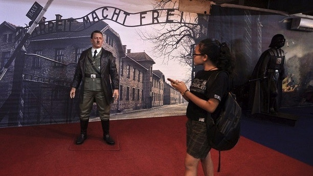 """In this Wednesday, Nov. 8, 2017 photo, a visitor walks past the wax figure of Adolf Hitler displayed against the backdrop of an image of Nazi Death Camp Auschwitz-Birkenau next to Star Wars character Darth Vader, right, at De Mata Museum in Yogyakarta, Indonesia. Rights groups have expressed outrage over the display of Hitler calling it """"sickening"""" and that """"it mocks the victims who went in and never came out."""" (AP Photo/Slamet Riyadi)"""
