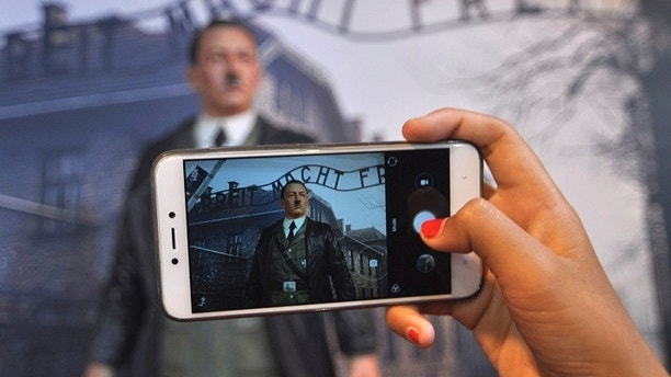 """In this Wednesday, Nov. 8, 2017 photo, a visitor uses her mobile phone to take a photo of the wax figure of Adolf Hitler displayed against the backdrop of an image of Nazi Death Camp Auschwitz-Birkenau at De Mata Museum in Yogyakarta, Indonesia. Rights groups have expressed outrage over the display calling it """"sickening"""" and demanded its immediate removal. (AP Photo/Slamet Riyadi)"""