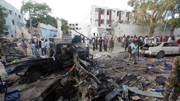 Rescue workers stand near the wreckage of vehicles in Mogadishu, Somalia, Sunday, Oct 29, 2017, after a car bomb was detonated  Saturday night. A Somali police officer said security forces ended a night-long siege at a Mogadishu hotel by attackers who stormed the building after a suicide car bomber detonated an explosives-laden vehicle at the entrance gate. (AP Photo/Farah Abdi Warsameh)