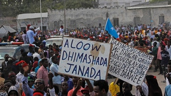 """Protesters march as they carry placards reading """"Out Al Shabab"""", left, and """"Oh God, have mercy on the dead"""" near the scene of Saturday's massive truck bomb attack in Mogadishu, Somalia, Wednesday, Oct. 18, 2017. Thousands of people took to the streets of Somalia's capital Wednesday in a show of defiance after the country's deadliest attack, as two people were arrested in connection with Saturday's massive truck bombing that killed more than 300. (AP Photo/Farah Abdi Warsameh)"""
