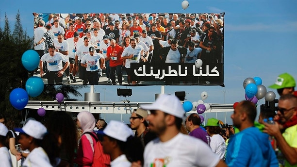 "Runners in the 8 km Beirut Marathon run past a billboard with a portrait of outgoing Lebanese Prime Minister Saad Hariri and Arabic that reads, ""We are all waiting for you,"" in Beirut, Lebanon, Sunday, Nov. 12, 2017. Absent from the marathon this year is Hariri, a regular participant, who resigned from his post unexpectedly last week while in Saudi Arabia. The country's President Michel Aoun urged runners to use the occasion to call on the prime minister to return home. (AP Photo/Hassan Ammar)"
