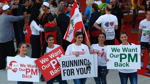 Lebanese women hold placards supporting the outgoing Lebanese Prime Minister Saad Hariri to return from Saudi Arabia during the Beirut Marathon in Beirut, Lebanon, Sunday, Nov. 12, 2017. Absent from the marathon this year is Hariri, a regular participant, who resigned from his post unexpectedly last week while in Saudi Arabia. The country's President Michel Aoun urged runners to call on the prime minister to return home. (AP Photo/Hassan Ammar)
