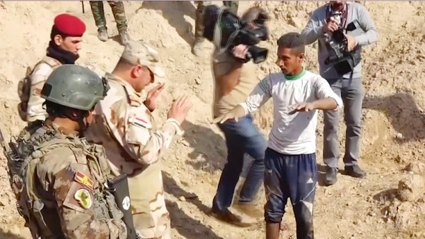 In this Saturday, Nov. 11, 2017 frame grab from video, Iraqi security forces speak to shepherd Khalaf Luhaibi next to bones on the ground, in an area recently retaken from the Islamic State group, at an abandoned base near the northern town of Hawija, Iraq. Kirkuk governor Rakan Saed said Sunday that the bodies of civilians and security forces have been found at the mass grave that could contain up to 400 bodies. (Kirkuk Governor's Office via AP)