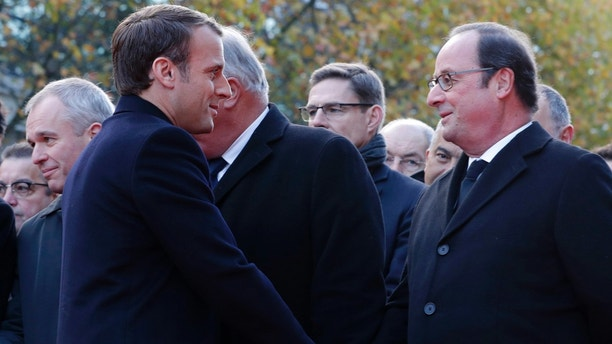 French President Emmanuel Macron, left, shakes hands with former French President Francois Hollande as they stand in front of a commemorative plaque outside the Stade de France stadium, in Saint-Denis, near Paris, Monday, Nov. 13, 2017. French President Emmanuel Macron, Paris Mayor Anne Hidalgo and victims' families are paying homage to 130 people killed two years ago when Islamic State extremists attacked the City of Light. (Philippe Wojazer, Pool via AP)