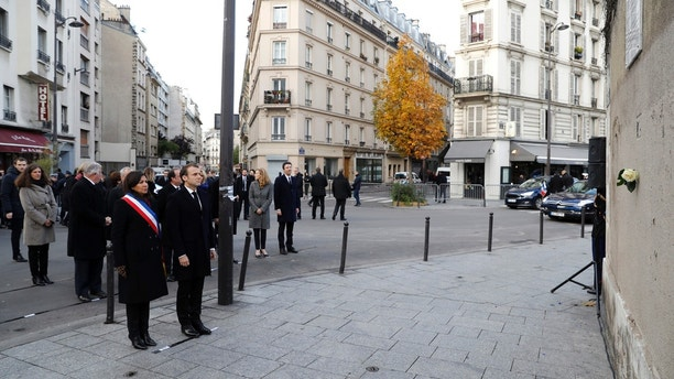 French President Emmanuel Macron and Paris mayor Anne Hidalgo, left, stand in front of a commemorative plaque facing the 'Le Carillon' bar and 'Le Petit Cambodge' restaurant during a ceremony marking the second anniversary of the Paris attacks, Monday Nov.13 November 2017. Macron, Paris Mayor Anne Hidalgo and victims' families are paying homage to 130 people killed two years ago when Islamic State extremists attacked the City of Light. (Etienne Laurent, Pool via AP)