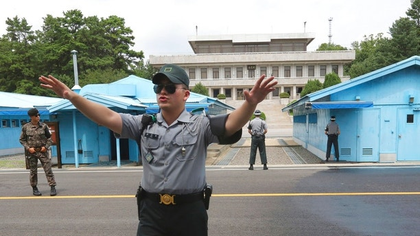 FILE - In this July 19, 2017, file photo, a South Korea army soldier gestures at the border villages of Panmunjom in Paju, South Korea. North Korean soldiers shot at and wounded a fellow soldier who was crossing a border village in an attempt to defect to South Korea on Monday, Nov. 13, 2017, the South's military said. (AP Photo/Ahn Young-joon, File)