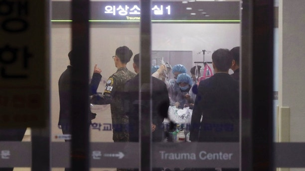 A South Korean army soldier, second from left, is seen as medical members treat an unidentified injured person, believed to be a North Korean soldier, at a hospital in Suwon, South Korea, Monday, Nov. 13, 2017. North Korean soldiers shot at and wounded a fellow soldier who was crossing a jointly controlled area at the heavily guarded border to defect to South Korea on Monday, the South's military said. (Hong Ki-won/Yonhap via AP)