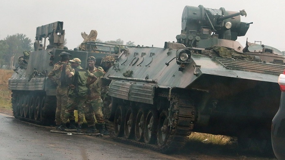 Soldiers stand beside a military vehicle outside Harare, Zimbabwe.