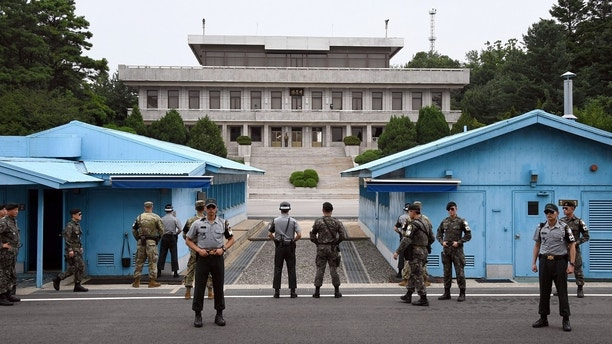 South Korea and U.S. soldiers stand guard during a commemorative ceremony for the 64th anniversary of the Korean armistice at the truce village of Panmunjom in the Demilitarized Zone (DMZ) dividing the two Koreas July 27, 2017. REUTERS/Jung Yeon-Je/Pool - RC14332F6BF0