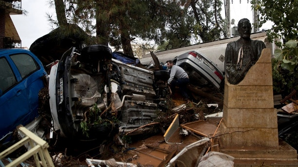 A car owner looks at a pile of vehicles in the municipality of Madra western Athens, on Wednesday, Nov. 15, 2017. Flash floods in the Greek capital's western outskirts Wednesday turned roads into raging torrents of mud and debris, killing at least nine people, inundating homes and businesses and knocking out a section of a highway. (AP Photo/Petros Giannakouris)