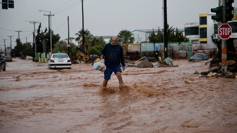 A man walks on a flooded street in the municipality of Mandra western Athens, on Wednesday, Nov. 15, 2017. Flash floods in the Greek capital's western outskirts Wednesday turned roads into raging torrents of mud and debris, killing at least nine people, inundating homes and businesses and knocking out a section of a highway. (AP Photo/Petros Giannakouris)