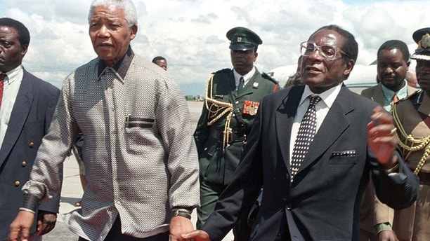 President Robert Mugabe of Zimbabwe (R) holds hands with his South African counterpart Nelson Mandela greeting him on his arrival in the country December 13. Mandela was here to address the 8th Assembly of the World Council of Churches which ends December 14.