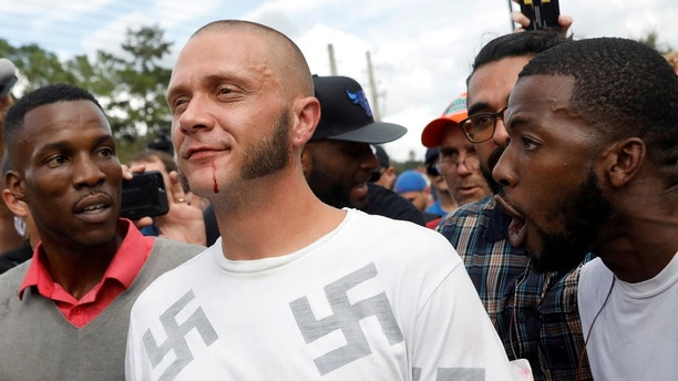 "A man walks with a bloody lip as demonstrators yell at him outside the location where Richard Spencer, an avowed white nationalist and spokesperson for the so-called alt-right movement, is delivering a speech on the campus of the University of Florida in Gainesville, Florida, U.S., October 19, 2017. REUTERS/Shannon Stapleton/File photo  SEARCH ""ALT-RIGHT FLORIDA"" FOR THIS STORY. SEARCH ""WIDER IMAGE"" FOR ALL STORIES. TPX IMAGES OF THE DAY. - RC148675D100"