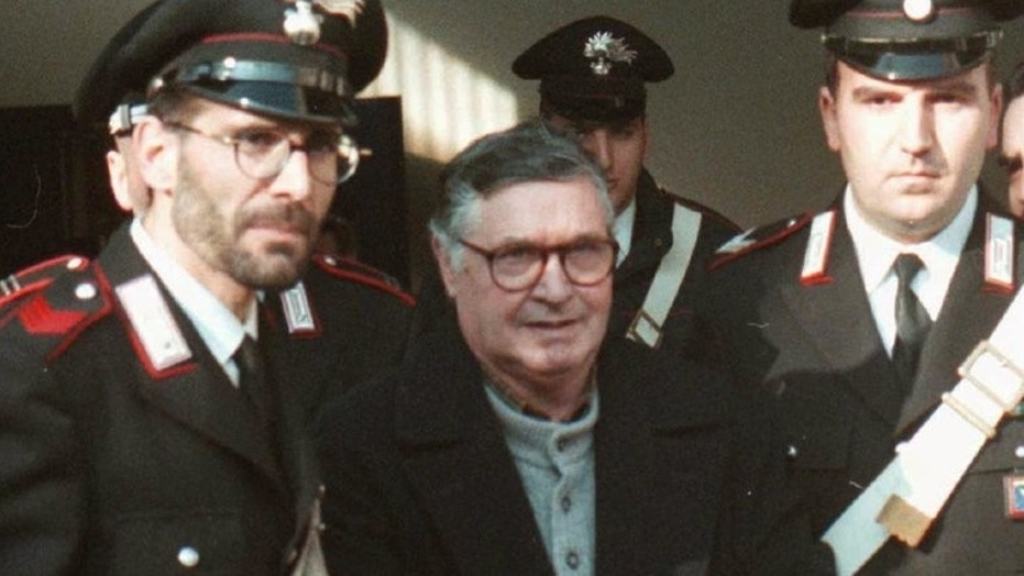 Mafia ″boss of bosses″ Salvatore ″Toto″ Riina, center, enters handcuffed into Bologna's bunker-courtroom, escorted by Carabinieri, Italian paramiliary police, in Bologna, Italy, in January 1996.